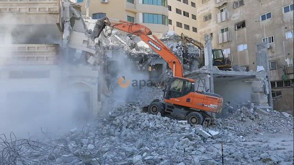 Palestinian workers use a bulldozer to remove the rubbles of a building which was hit by Israeli strikes during the recent conflict between Israel and Hamas