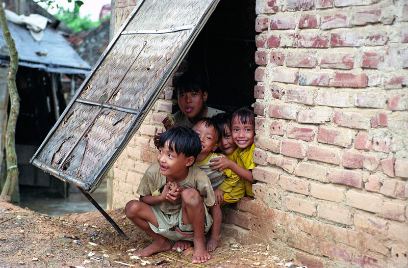 Kids clamor to the doorway to view the American tourists. Kenh Ga Village south of Hanoi, 2001.