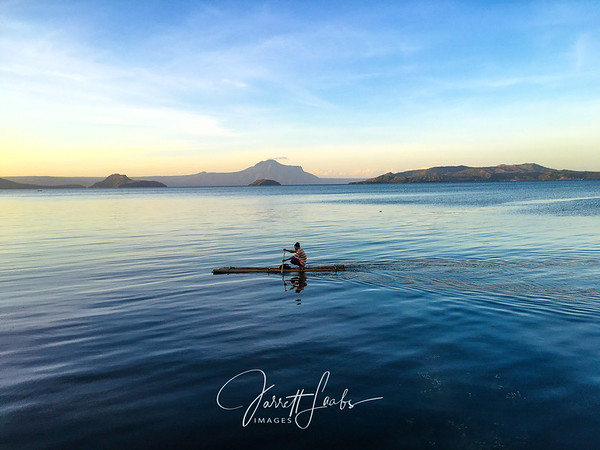 A Filipino fisherman paddles out to check his nets on Taal Lake in Tagaytay, Philippines