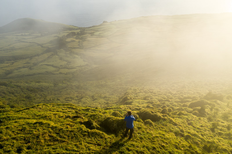 Photographer shooting at sunrise with a tripod on a misty morning on Pico Island