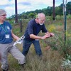 Meegan Wallace and Charles Deffenbaugh (Chuck) from JCC  taking photo of a butterfly on an Aster, near garden plot