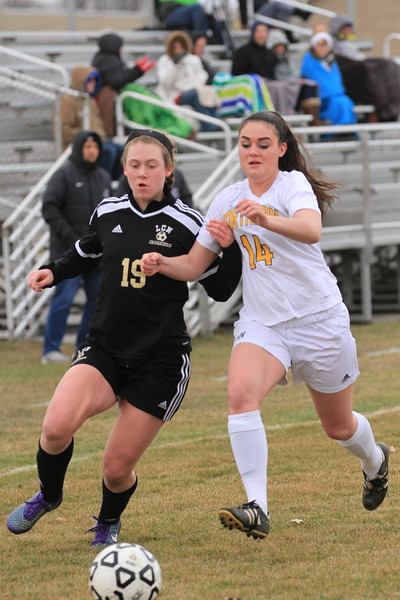L'Anse Creuse North's Caitlin O'Malley (19) and Port Huron Northern's Lily Hayes (14) race for possession during the first half. O'Malley scored twice in a 3-1 victory. (MIPrepZone photo gallery by Randy Castro)