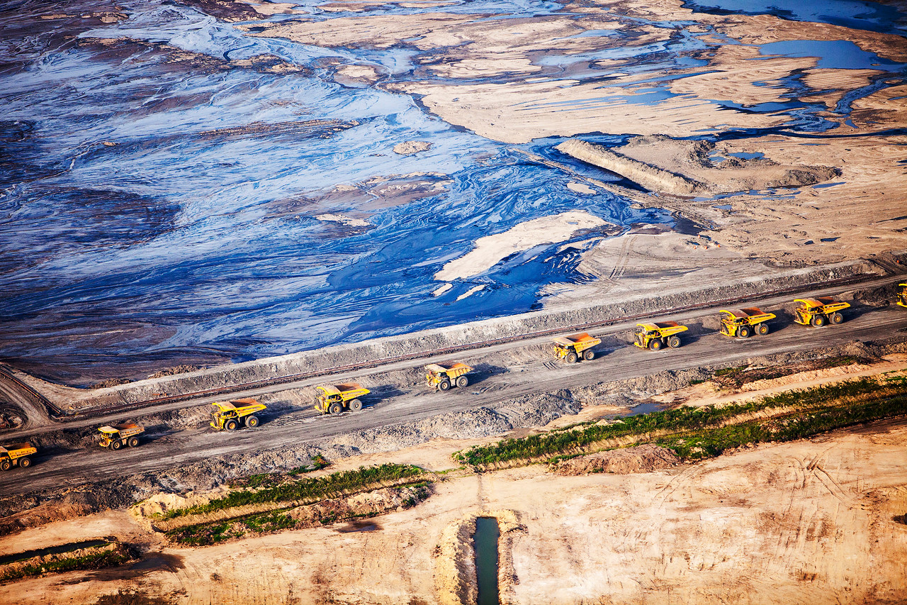 Massive dump trucks queue up to load with tar sand in front of a toxic wasteland. For McMurray, Canada.