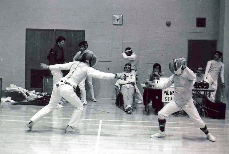 Chris Moore fencing on the right.  Harry Stone seated behind the weapons.  Allan Hancock seated by scoring machine.  Wayne Galella standing, far right.