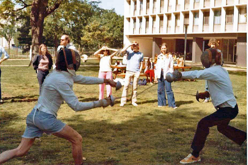 Two weapon fencing at club picnic (Harry Stone, left, and Bill Jenkins).  Melinda (Mayfield) Stone, Dale Sweeney, Carole Fernandez, JohnTurnley, Dawn Miller and Andy Auerbach (mostly hidden) in the background, from left.