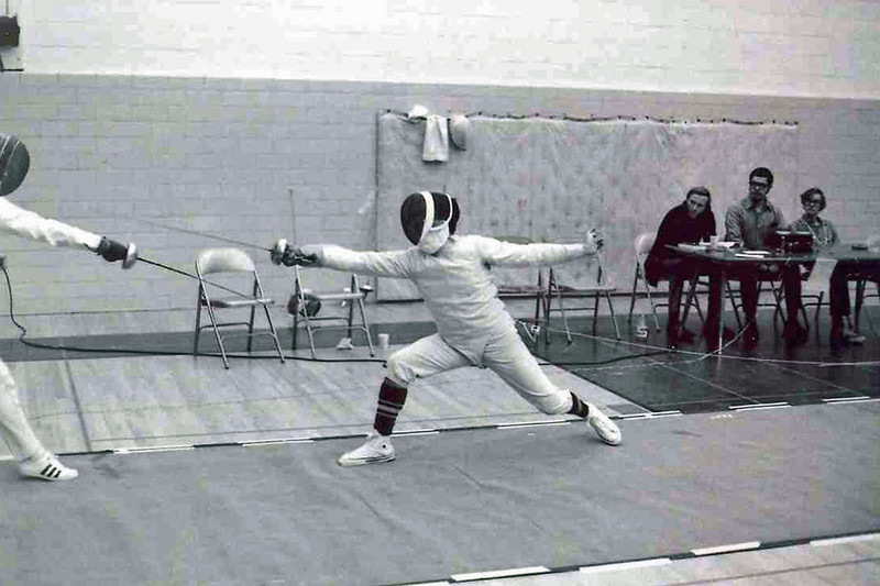 Chris Moore fencing on strip on right.  James Hunter and Steve Block seated at the table.