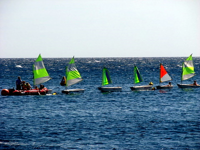 Kids in mini sail boats learning how to sail