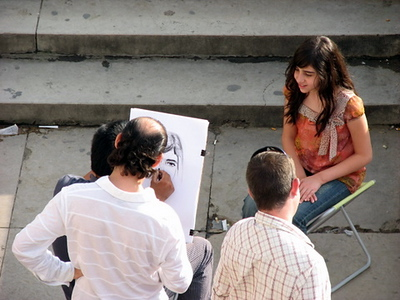 Girl getting her portrait done by 1 of the 1,000,000,000,000 artists doing them around the city
