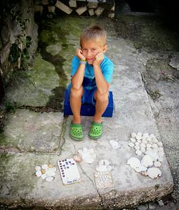 Little kid selling sea shells