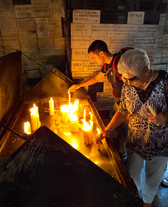 People lighting candles to Mary - the patron saint of Zagreb.  When the house here burned in 1731, the only thing left standing was a portrait of Mary.  It has become a make shift chapel .