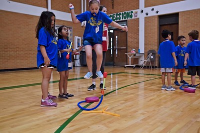 Juliet Hart jumps and launches a foam rocket into the air as friends watch during Vacation Bible School June 15 at St. Patrick Parish in Dallas.