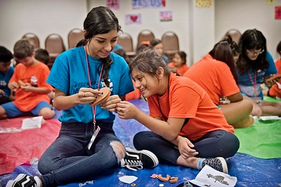 Teen Kathy Blanco helps Jayla Garcia with an arts and crafts project during Vacation Bible School June 27 at St. Paul the Apostle Parish in Richardson.