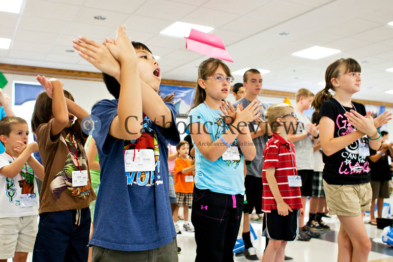 Logan Kenney, 9, does the hand movements that accompany a song during Vacation Bible School at St. Ignatious, Hickory June 28.