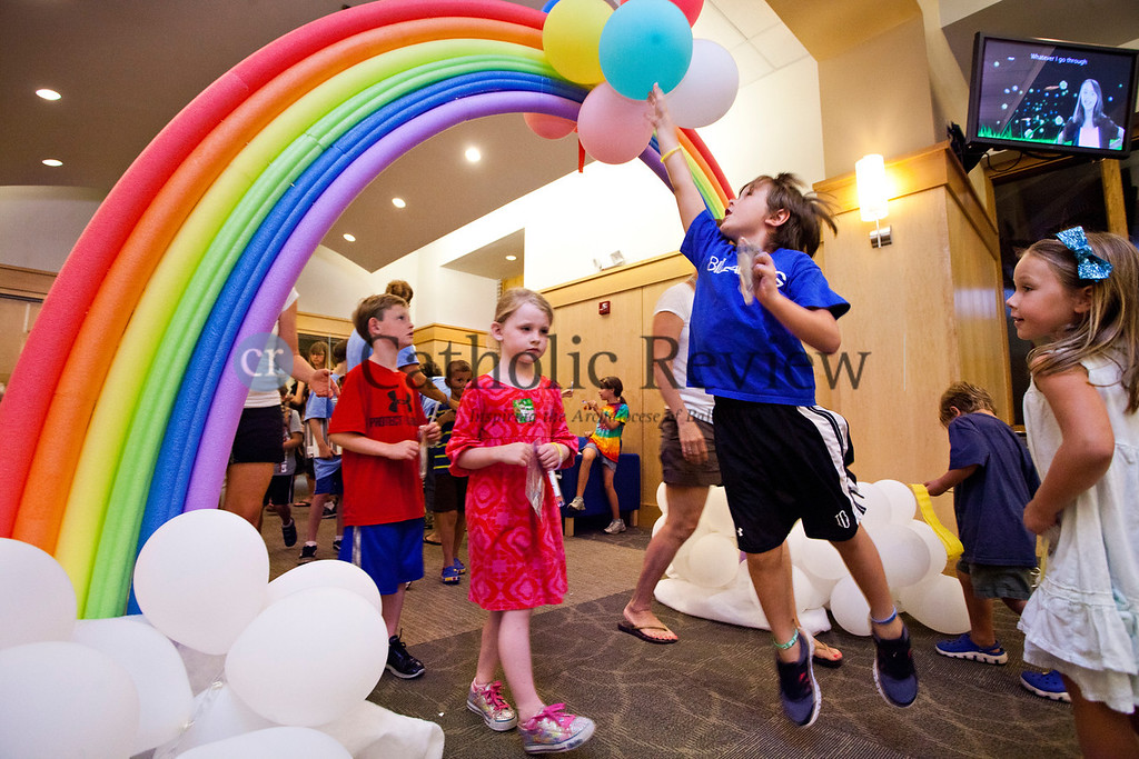 Grady O'Day, 6, leaps into the air to touch the balloons hanging from the rainbow archway at the entrance to the Vacation Bible School at the Church of the Nativity in Timonium June 28.