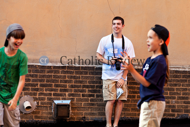 Zach Bowman, a parishioner of the Catholic Community of South Baltimore who creates the scenery for the Vacation Bible Schools,  captures images from the day's events June 26 for an end of the day slideshow presentation.
