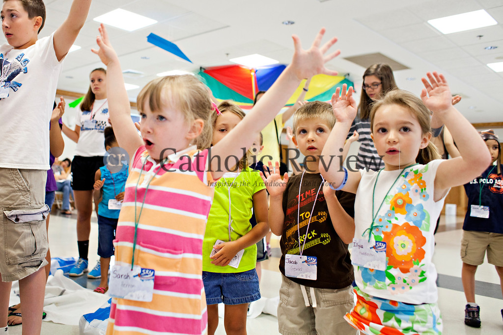 Sarah Herron, Jacob Gensel and Ilyia Huddleston raise their arms as they join in singing a song during Vacation Bible School at St. Ignatious, Hickory June 28.