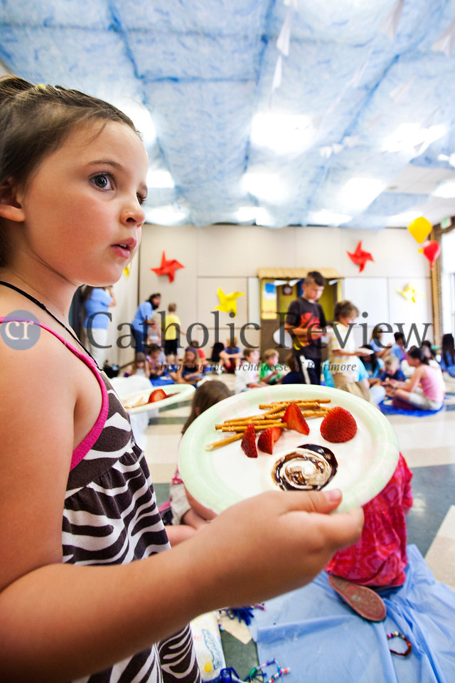 Kieran Carney, 5, serves her fellow campers snack plates of pretzels., strawberries and a fruit dip and chocolate swirl to symbolize the impossibility of seperating God's love the Church of the Nativity in Timonium June 28.