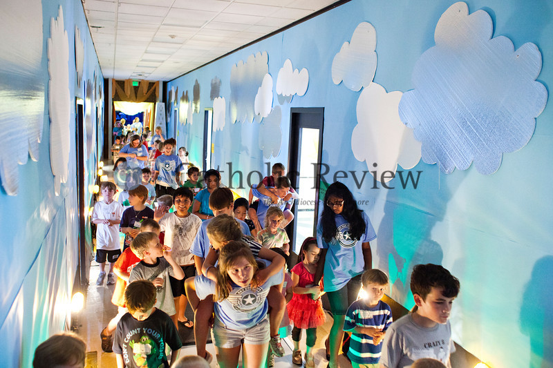 """Vacation Bible School students and counselors walk down the creatively lit and decorated """"runway"""" at the Church of the Nativity in Timonium June 28."""