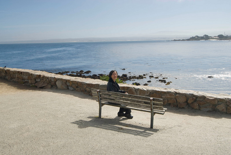 Kim sits on a bench in my favorite public park on the Monterrey Bay side of the peninsula.