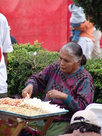 Making Snacks in the street for sale.  They were being bought up quickly.