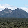 A butte with a bunch of government antenna located on top.