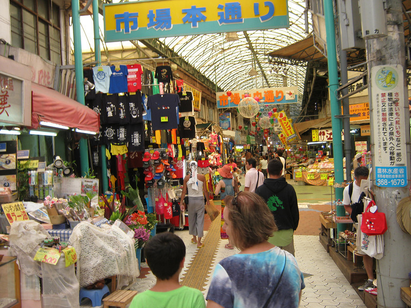 Interior of a Okinawan market, with a giant fish market in the middle area.  Cars and scooters regularly go down the center lanes.  The ceiling is just over the road, similar to Vegas's Strip.