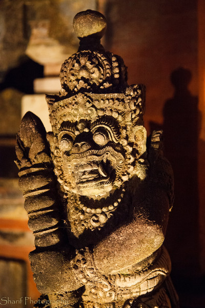 A statue guards the entrance of a temple against evil spirits.