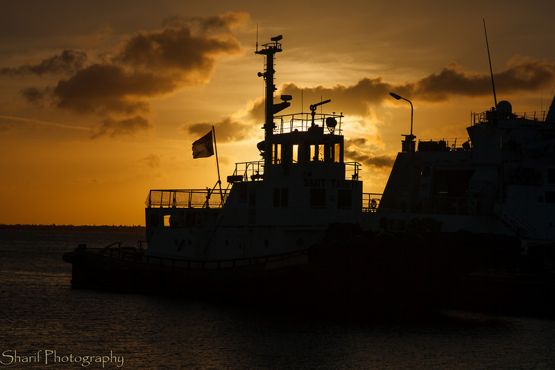 A tugboat is silhouetted against the sunset.