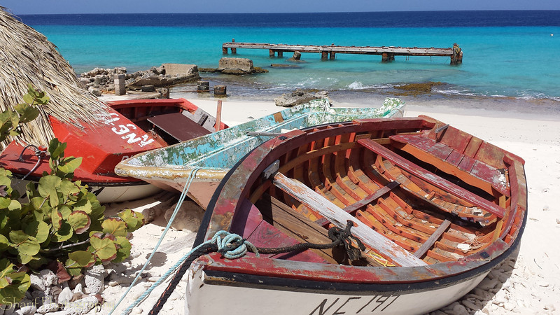 A collection of old boats and a decrepid pier on Klein Curacao.