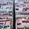 A narrow street of tall buildings splits the city