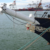 At the Dock.<br /> The bow of the STS (Sail Training Ship) Leeuwin II and the port beyond.
