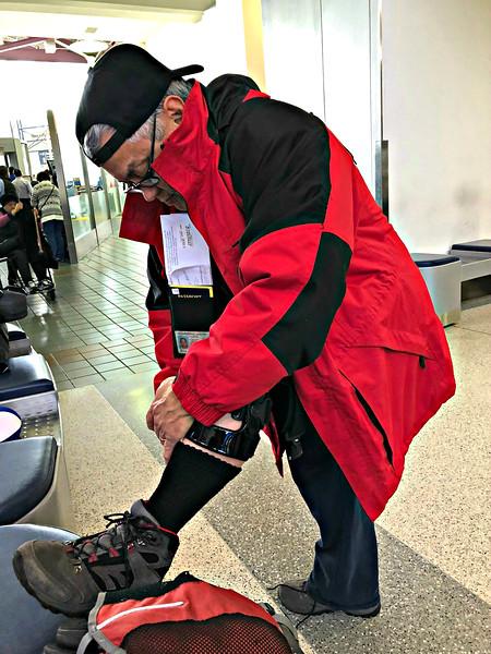 Sam adjusting his knee brace at the airport.