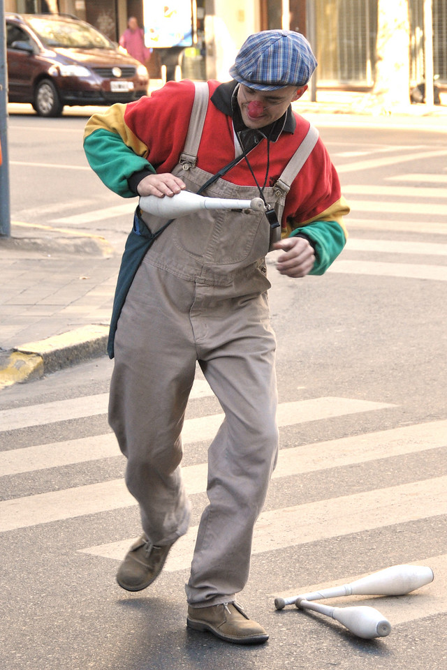 A street performer does his act during a stop at a red light.