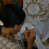 Demonstration of applying wax with a canting to create a batik design at Sari Amerta Batik Colection
