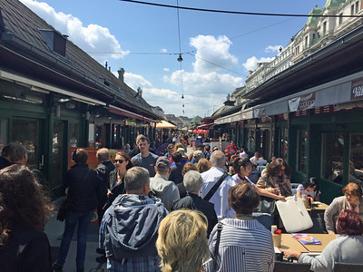 Walking down the main aisle of the Naschmarkt with restaurants on either side.