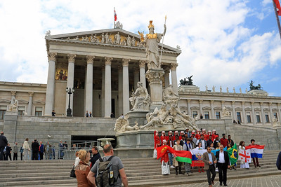 A colorful group of young people pose for a picture in front of the Austrian Parliament Building.