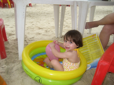 She hated the sand on her feet so she sat in this little plastic pool.