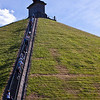 "Waterloo - Belgique<br /> Butte du Lion<br /> <br /> The Battle of Waterloo was fought on Sunday 18 June 1815 near Waterloo in present-day Belgium, then part of the United Kingdom of the Netherlands. An Imperial French army under the command of Emperor Napoleon was defeated by combined armies of the Seventh Coalition, an Anglo-Allied army under the command of the Duke of Wellington combined with a Prussian army under the command of Gebhard von Blücher. It was the culminating battle of the Waterloo Campaign and Napoleon's last. The defeat at Waterloo put an end to Napoleon's rule as Emperor of the French and marked the end of his Hundred Days' return from exile.<br /> Upon Napoleon's return to power in 1815, many states that had opposed him formed the Seventh Coalition and began to mobilise armies. Two large forces under Wellington and von Blücher assembled close to the northeastern border of France. Napoleon chose to attack in the hope of destroying them before they could join in a coordinated invasion of France with other members of the Coalition. The decisive engagement of this three-day Waterloo Campaign (16–19 June 1815) occurred at the Battle of Waterloo. According to Wellington, the battle was ""the nearest-run thing you ever saw in your life.""[5]<br /> Napoleon delayed giving battle until noon on 18 June to allow the ground to dry. Wellington's army, positioned across the Brussels road on the Mont-Saint-Jean escarpment, withstood repeated attacks by the French, until, in the evening, the Prussians arrived in force and broke through Napoleon's right flank. At that moment, Wellington's Anglo-allied army counter-attacked and drove the French army in disorder from the field. Pursuing Coalition forces entered France and restored Louis XVIII to the French throne. Napoleon abdicated, surrendered to the British, and was exiled to Saint Helena, where he died in 1821.<br /> The battlefield is in present-day Belgium, about eight miles (12 km) SSE of Brussels, and about a mile (1.6 km) from the town of Waterloo. The site of the battlefield is today dominated by a large monument, the Lion Mound. As this mound used earth from the battlefield itself, the original topography of the part of the battlefield around the mound has not been preserved."