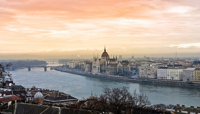 View of the Danube river and the House of Parliament in Budapest against a sunset sky.