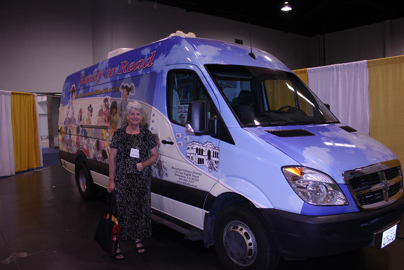 "June 23, 2012 (American Library Association 2012 Convention [Exhibit Hall] @ Anaheim Convention Center / Anaheim, Orange County, California) -- Mary Anne in front of the ""Parade of Bookmobiles"" exhibit"