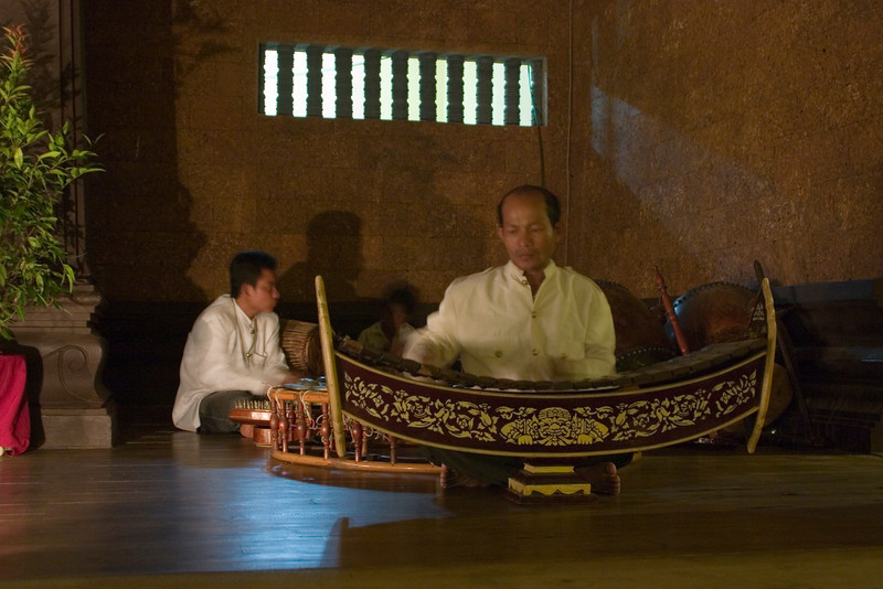 Musicians at Angkor Mondial Restaurant.   The xylophone-looking instrument is a Roneat Ek.   The bars the musician strikes are made of teak.