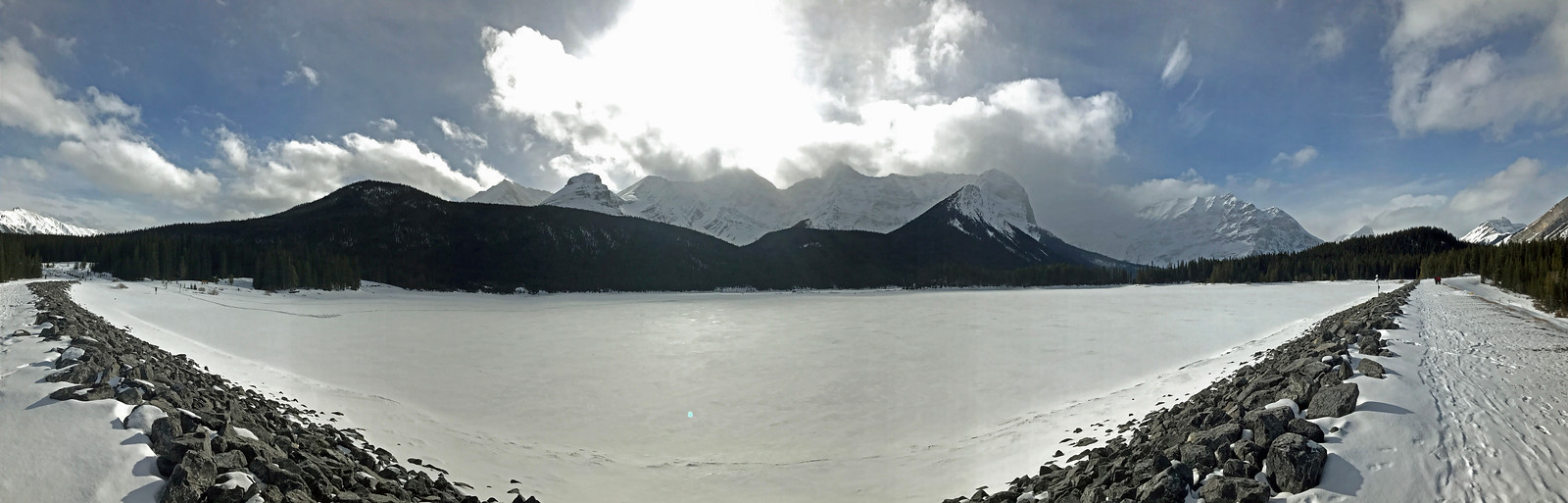 """The Upper Kananaskis Lake and surrounding mountains from the man-made dam that created the lake.  Rawson Lake is in the """"bowl"""" above the tree line just a little right of center."""