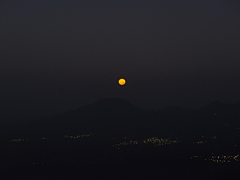 Moon setting behind volcano.
