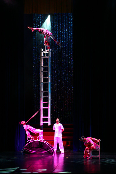 A stack of chairs with an acrobat on top, all supported by the lady below