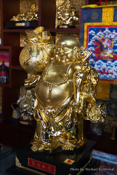 More small statues of the smiling Buddha.