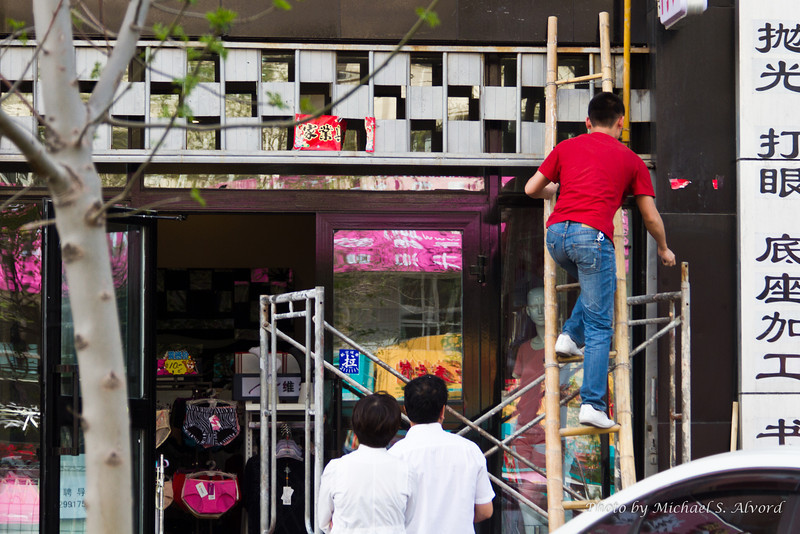 Everywhere you went it was a mix of old and new. Here a guy was repairing an electric sign using a bamboo ladder.