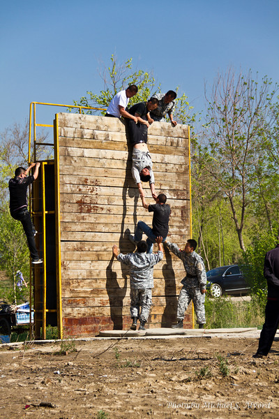 Like the previous pictures where the solders had people competing. These obstacles were setup just like military obstacles and show the solders having the people learn how to scale the wall.