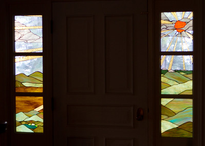 These delightful stained-glass sidelights flank the front door.