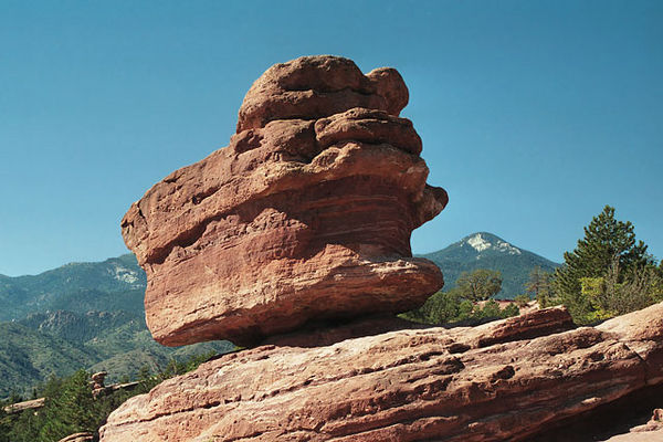 Balancing rock at the Garden of the Gods in Manitou Springs.<br /> The top portion of this rock looks to me like a human figure<br />  kneeling or sitting on their legs with their forehead bowed low.<br /> The back is up and the head is to the right.