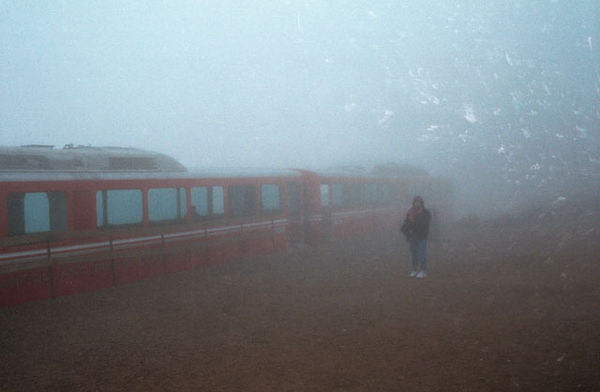 Becky waiting next to the cog train during the first snowstorm of winter on top of Pike's Peak.<br /> At the top, I was almost struck by lightening and then started feeling a bit dizzy from the altitude...<br /> I had to sit down for a few minutes-- Becky felt fine.